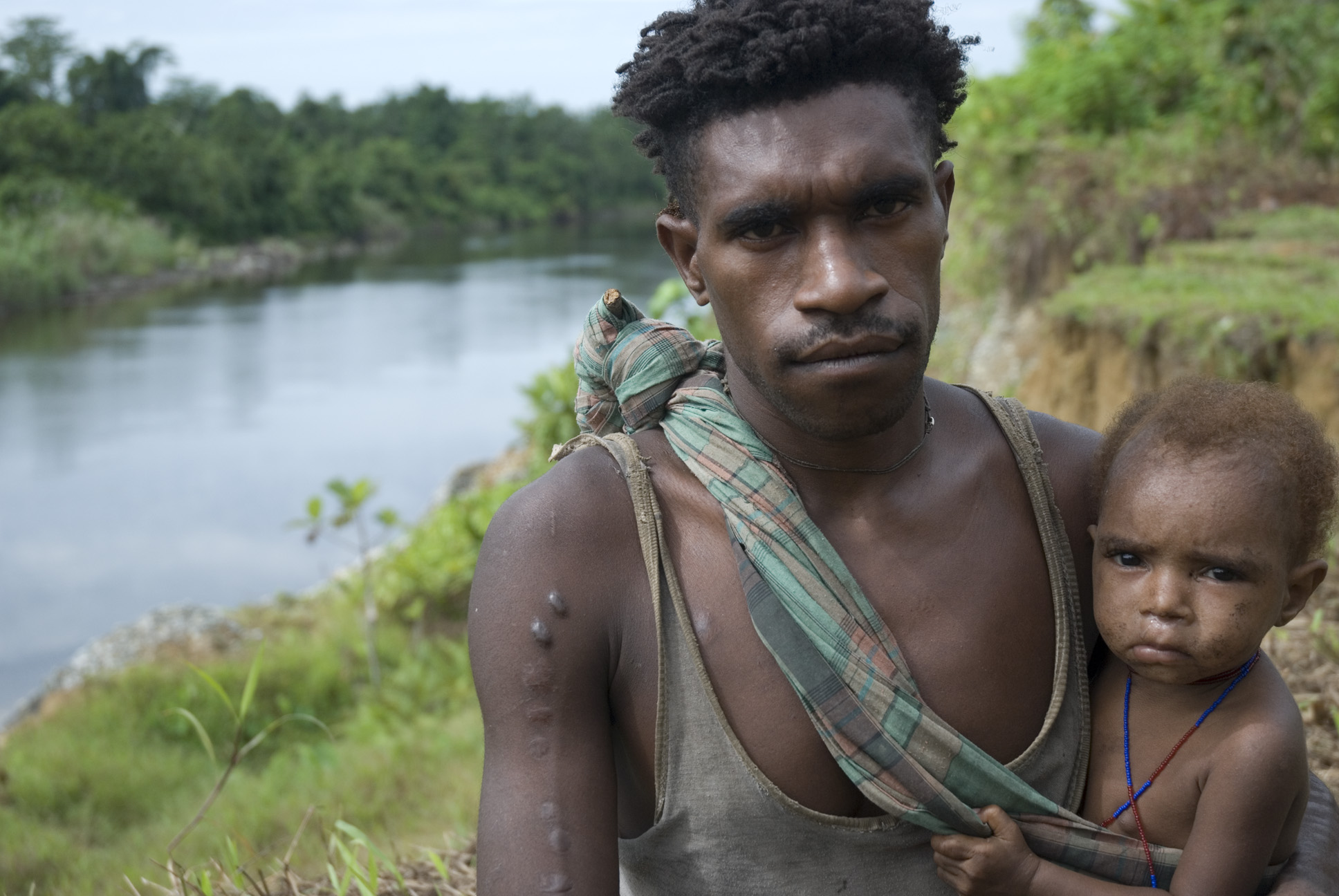 Ein Korowai Mann mit Kind in West Papua.