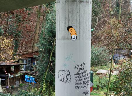 Säule mit Graffiti und Schrebergarten